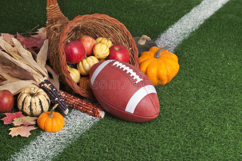College style Football with a cornucopia on grass field. A college style football with a cornucopia on a grass field with white stripe stock photography