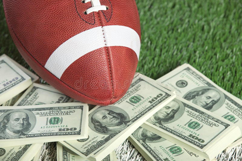 College style football on field with a pile of money. A college style football sits with a pile of money on a green field stock photography