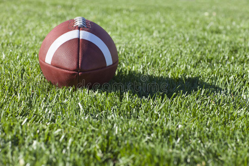 College style football on grass field. Selective focus, low angle view of a college style football on a grass field stock photos