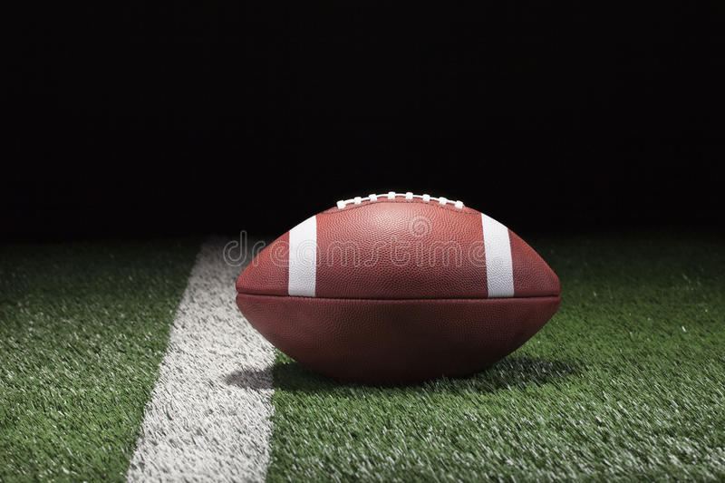 College style football on grass field and stripe at night. Low angle royalty free stock image