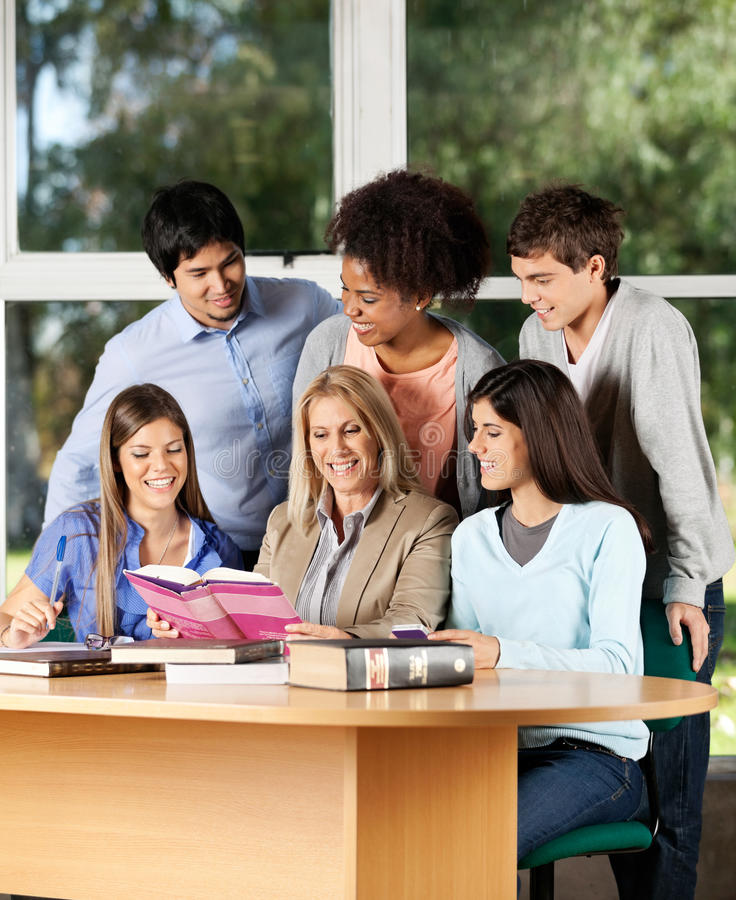 College Teacher Explaining Lesson To Students In stock photos