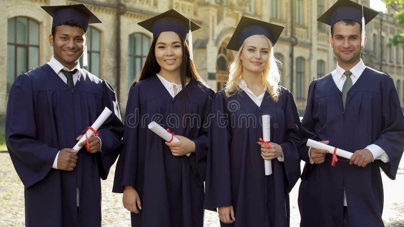 Collegeabsolvent in den akademischen Insignien, welche die Diplome, Staffelung feiernd halten stockfotos