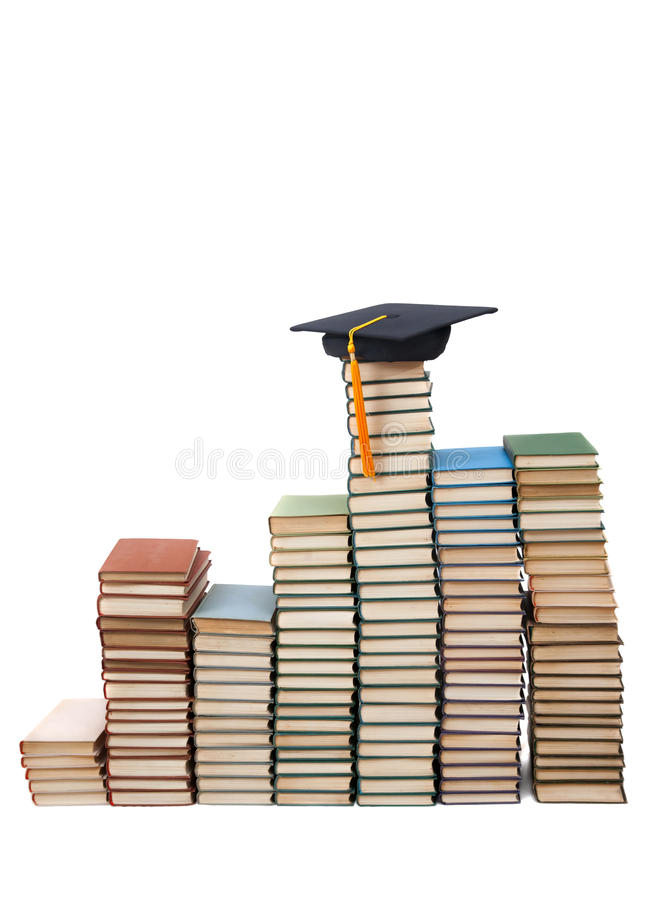 Collegekappe und Stapel der alten Bücher stockfotografie