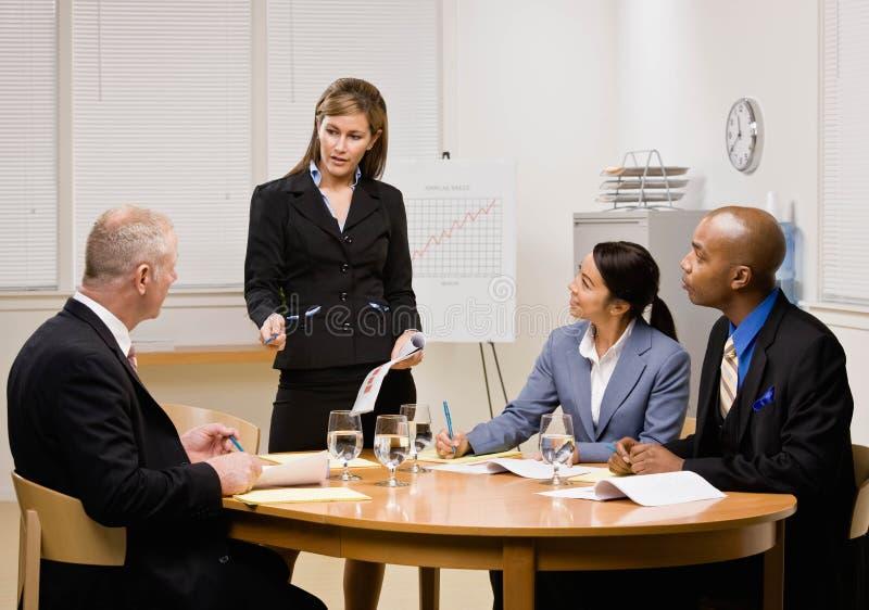 Colleghe che hanno riunione nella sala per conferenze immagine stock