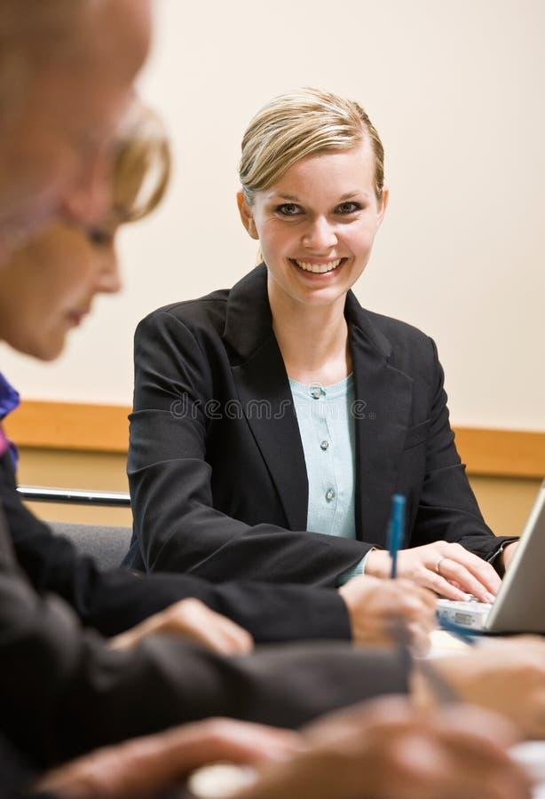 Colleghe che si incontrano alla tabella nella sala per conferenze fotografia stock libera da diritti