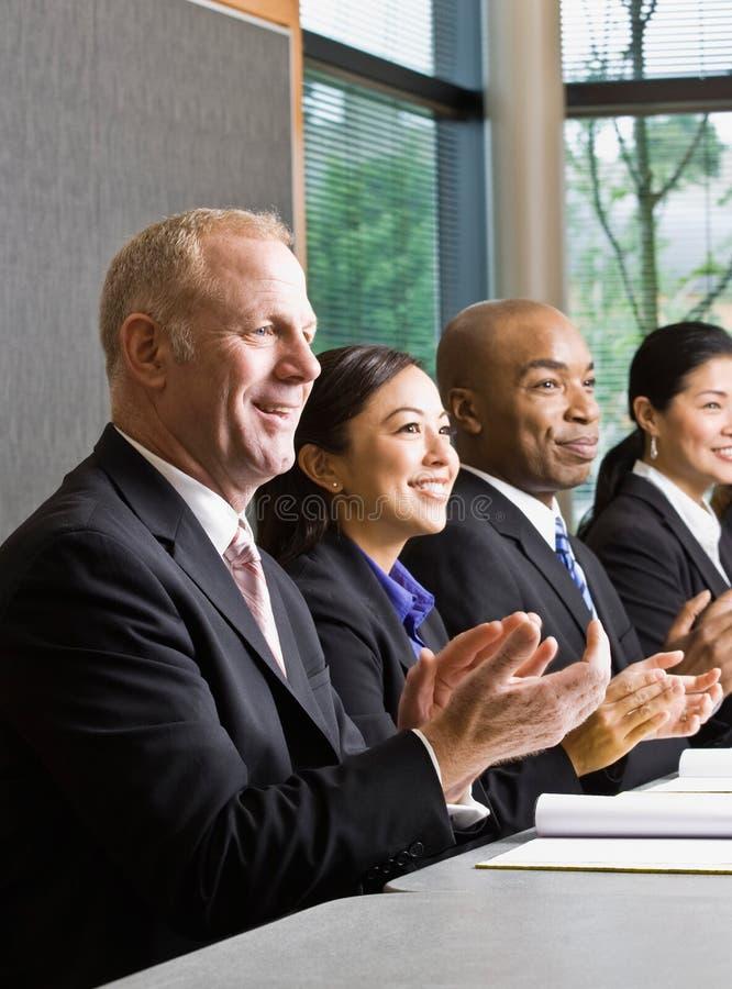 Colleghe che si siedono in una riga, applaudente fotografia stock libera da diritti