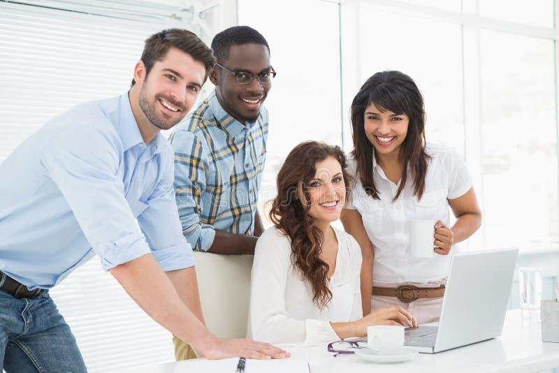 Colleghe felici che collaborano con il computer portatile fotografia stock libera da diritti