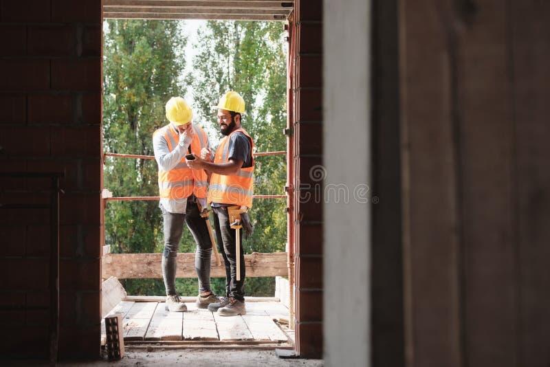 Colleghe felici che ridono con Smartphone nel cantiere immagine stock libera da diritti