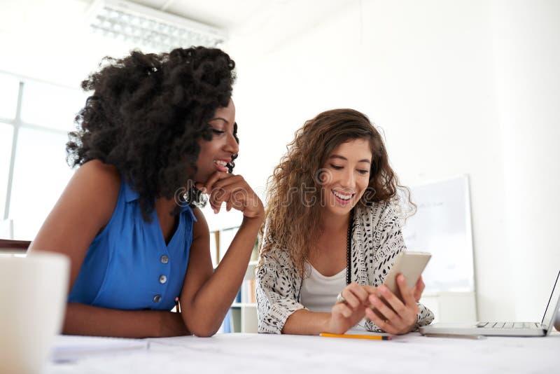 Colleghe sorridenti con Smartphone immagine stock libera da diritti
