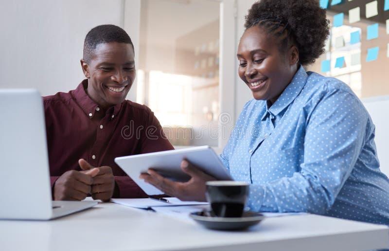 Colleghi africani che lavorano con una compressa nell'ufficio di affari fotografia stock libera da diritti