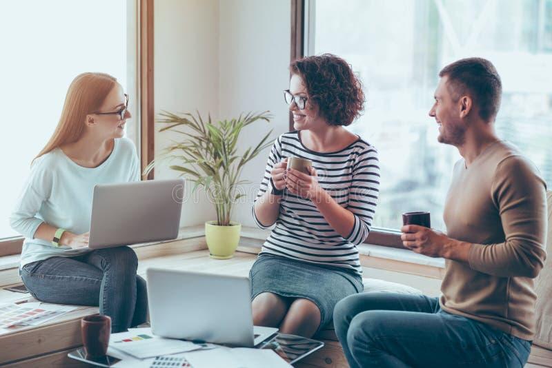 Colleghi allegri che bevono caffè nell'ufficio immagini stock libere da diritti