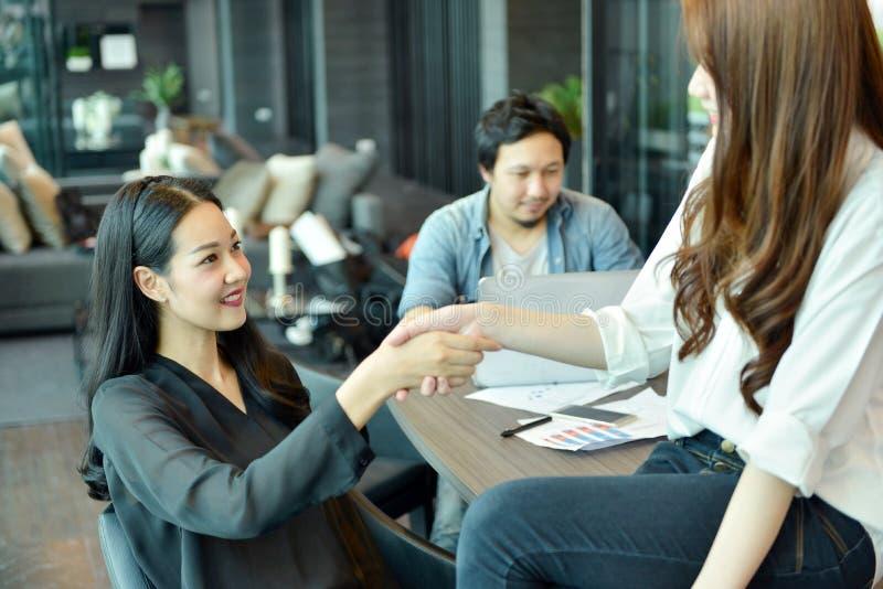 Colleghi asiatici di affari che stringono le mani in ufficio fotografia stock libera da diritti