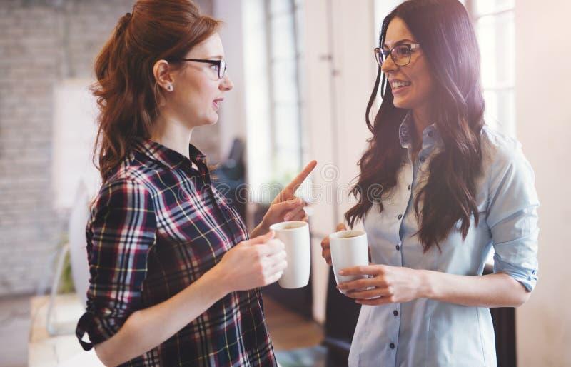 Colleghi che hanno pausa caffè in ufficio moderno fotografie stock libere da diritti