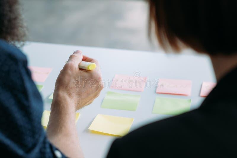 Colleghi che incontrano coworking confrontando le idee le note immagini stock