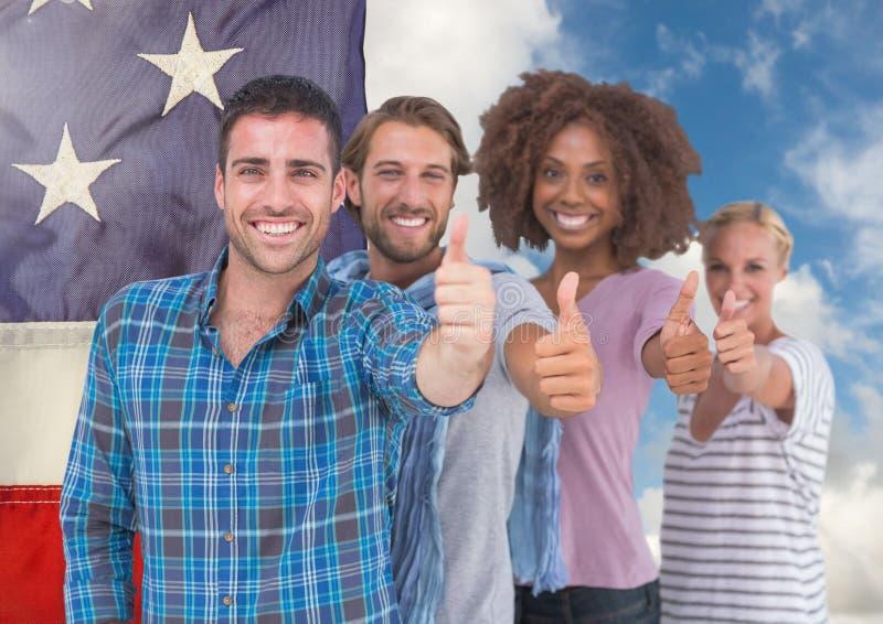 Colleghi che mostrano i pollici su contro la bandiera americana in cielo immagine stock