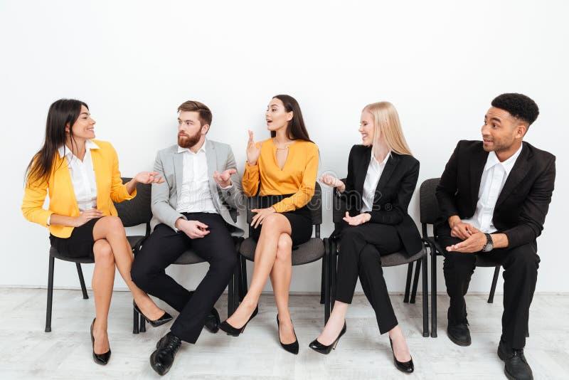 Colleghi che si siedono nell'ufficio che parla a vicenda immagini stock