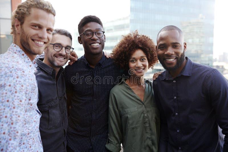 Colleghi creativi felici di affari che sorridono alla macchina fotografica all'aperto, vita su, fine su fotografia stock