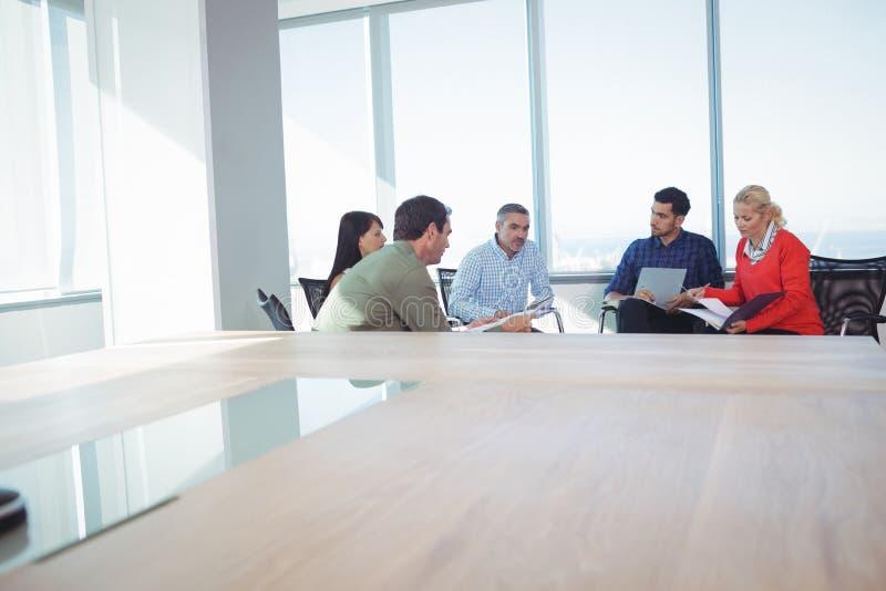 Colleghi di affari che discutono mentre sedendosi contro la finestra all'ufficio fotografie stock libere da diritti