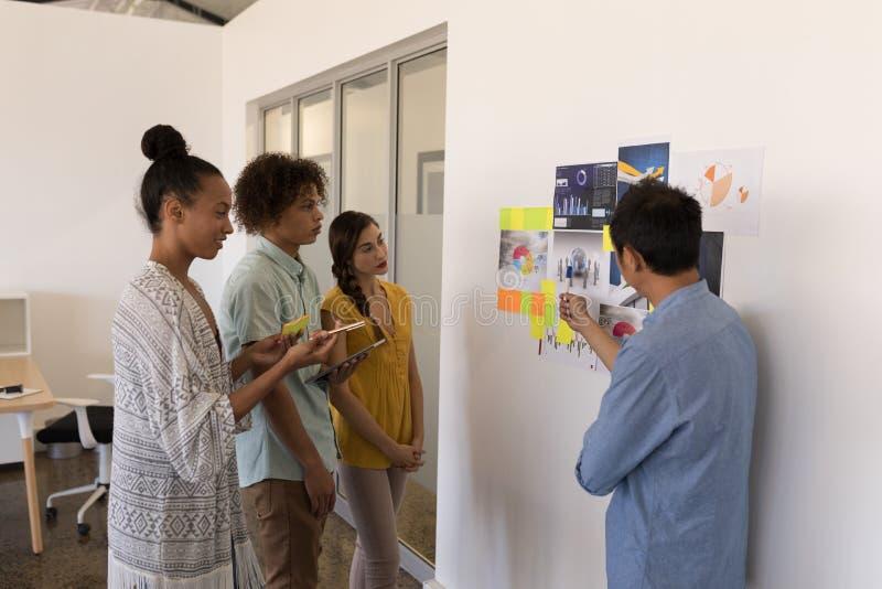 Colleghi di affari che discutono sopra i grafici e le note appiccicose nell'ufficio fotografie stock libere da diritti