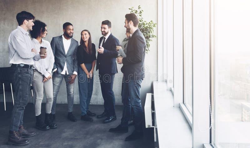 Colleghi di affari che hanno pausa caffè vicino alla finestra fotografie stock libere da diritti