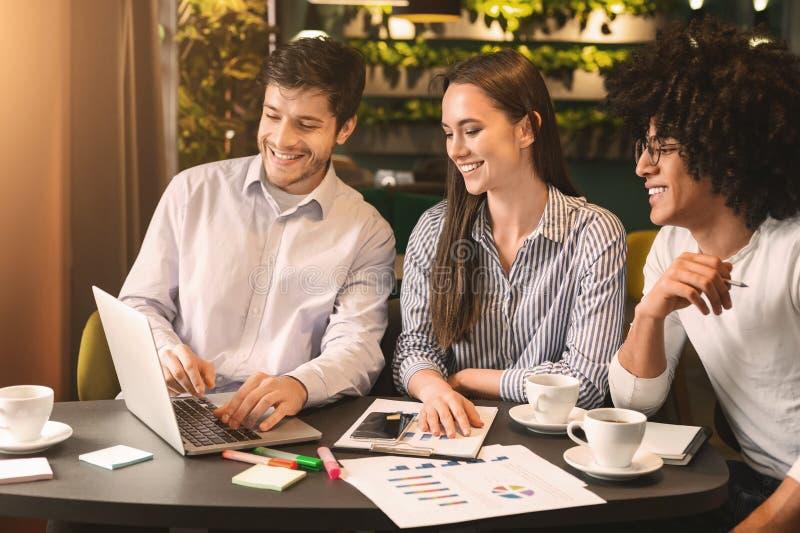 Colleghi di affari che lavorano insieme con la presentazione al caffè fotografia stock