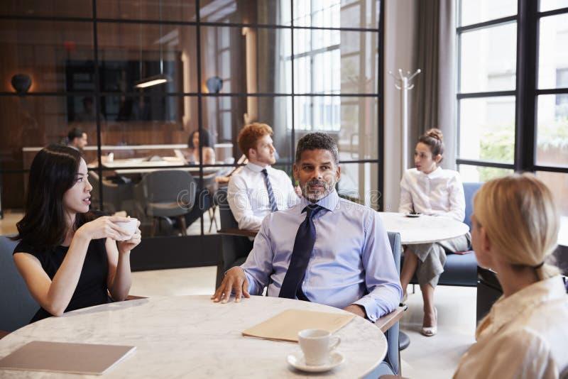 Colleghi di affari che parlano al loro caffè dell'ufficio immagine stock