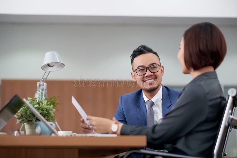Colleghi di affari che parlano l'un l'altro all'ufficio immagine stock libera da diritti