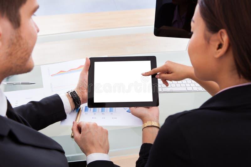 Colleghi di affari che per mezzo della compressa digitale fotografia stock