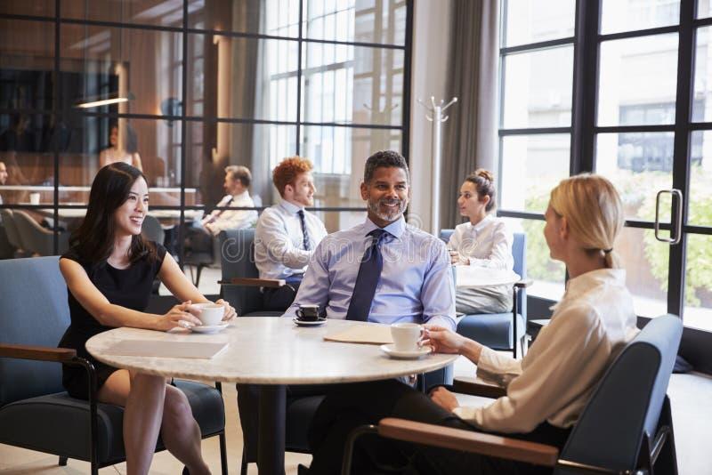 Colleghi di affari che si rilassano al loro caffè dell'ufficio fotografia stock libera da diritti
