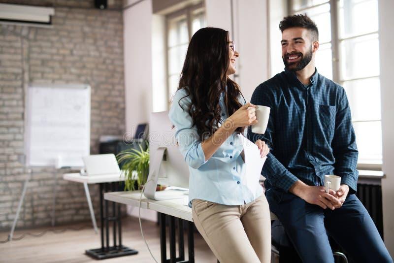 Colleghi di Coworking che hanno conversazione nel luogo di lavoro immagini stock