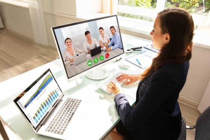 Colleghi di Videoconferencing With Her della donna di affari sul computer immagini stock libere da diritti