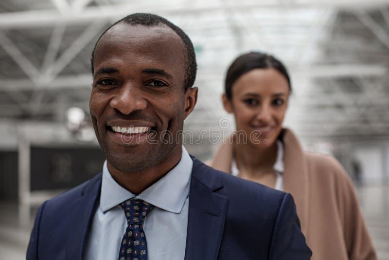 In colleghi esperti piacevoli stanno posando con il sorriso fotografie stock