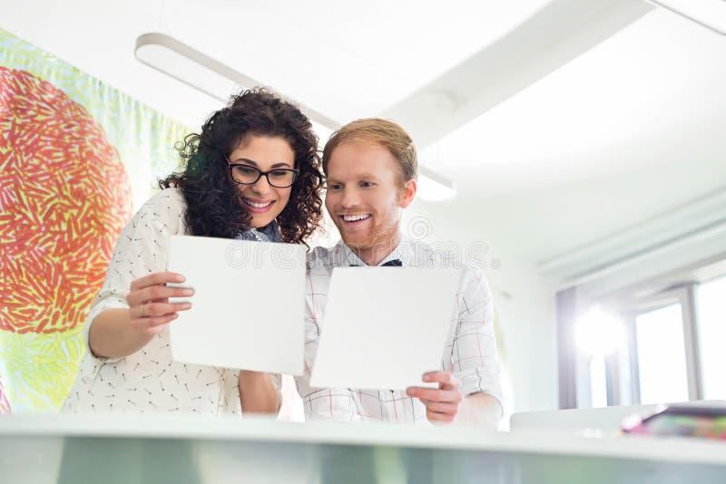 Colleghi felici di affari che esaminano i campioni in ufficio creativo immagini stock libere da diritti