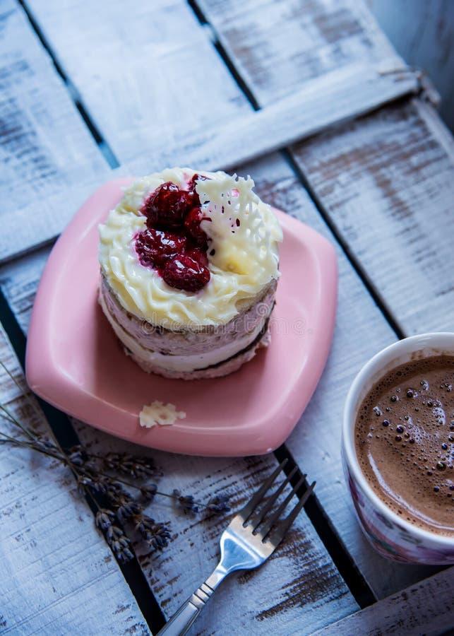 Colleghi il dolce con cioccolata bianca ed i lamponi su un piatto e su una tazza rosa con cioccolata calda fotografia stock