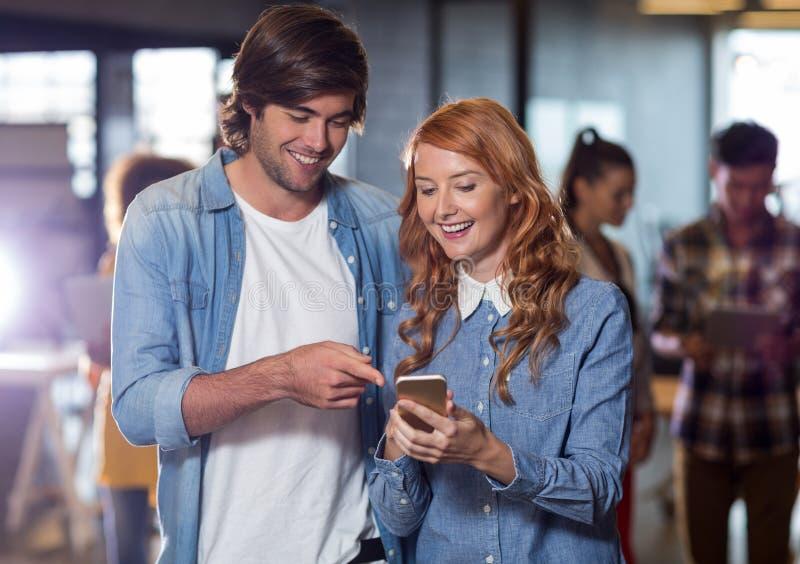 Colleghi sorridenti che discutono mentre utilizzando telefono cellulare nell'ufficio immagini stock libere da diritti