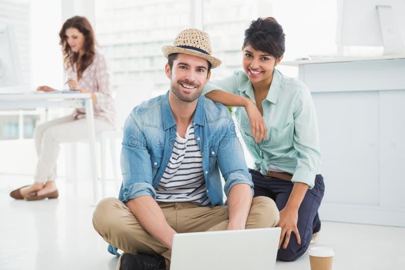 Colleghi sorridenti che si siedono sul pavimento facendo uso del computer portatile fotografia stock