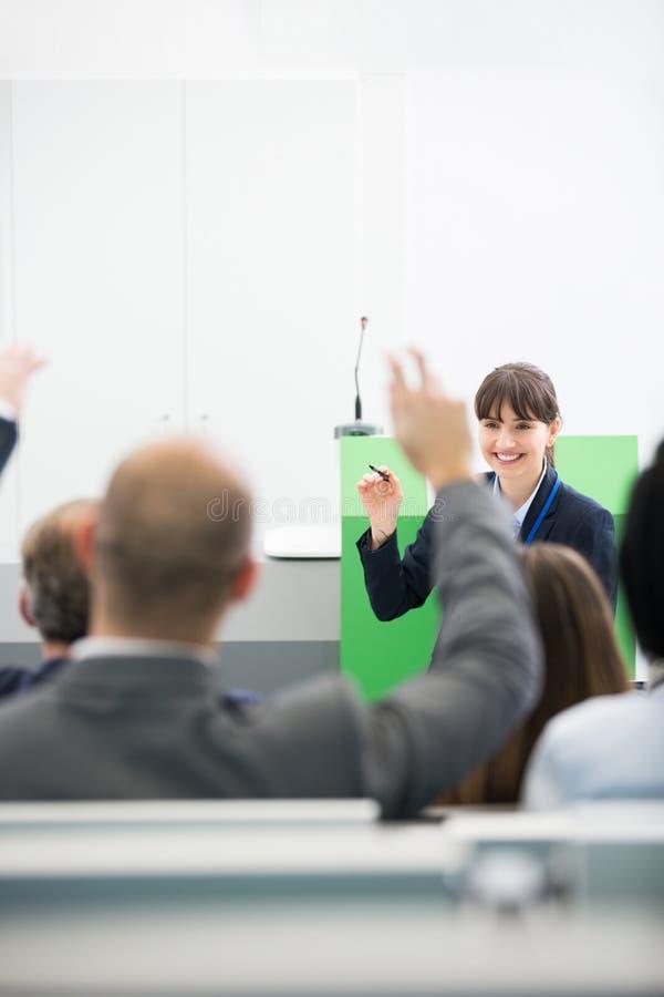 Colleghi sorridenti di Asking Questions To della donna di affari mentre Givin fotografie stock