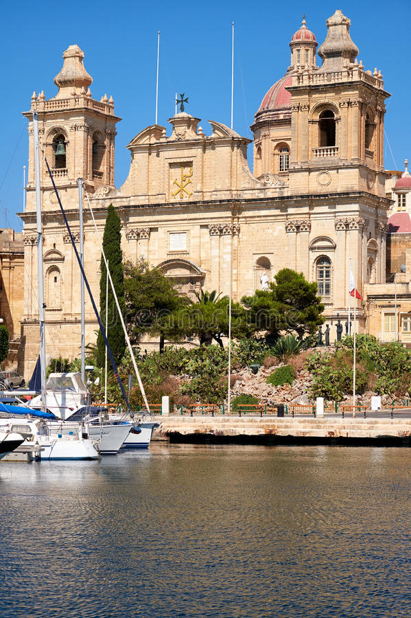 The Collegiate church of St Lawrence in Birgu, Malta. The view of Collegiate church of St Lawrence over the water of Dockyard creek. The church of St Lawrence is stock image