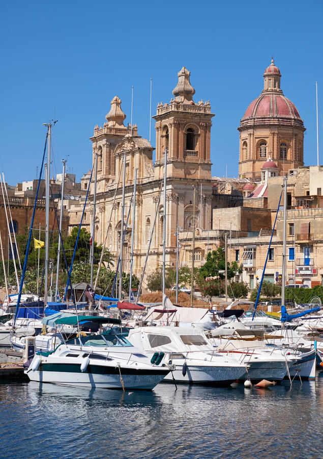 The Collegiate church of St Lawrence in Birgu, Malta. The view of Collegiate church of St Lawrence over the water of Dockyard creek with yachts moored in the stock photos