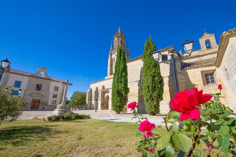 Ancient cross and San Miguel Collegiate in Ampudia village royalty free stock photography