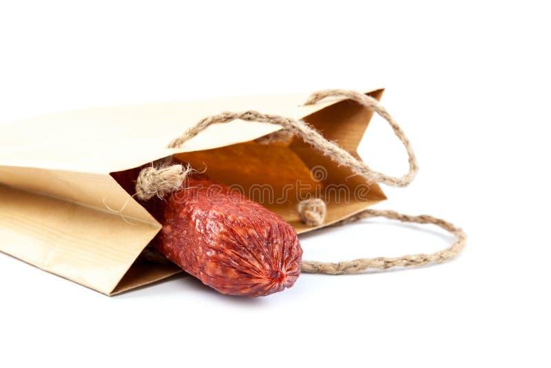 Collez la saucisse dans un sac de papier sur un fond blanc images libres de droits