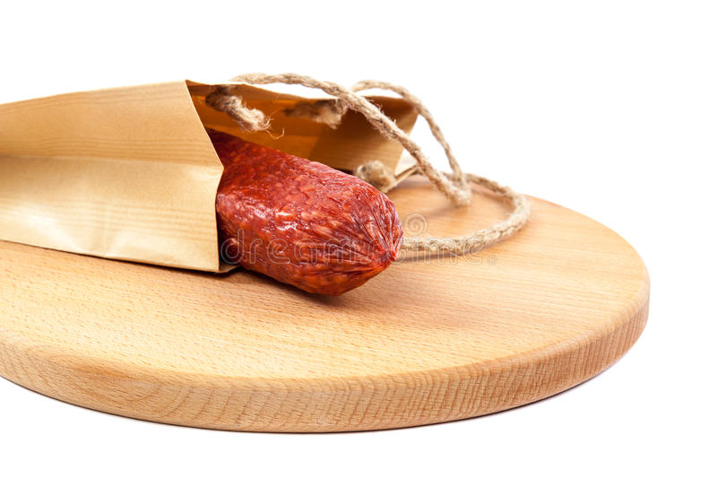 Collez la saucisse dans un sac de papier sur une planche à découper en bois photo libre de droits