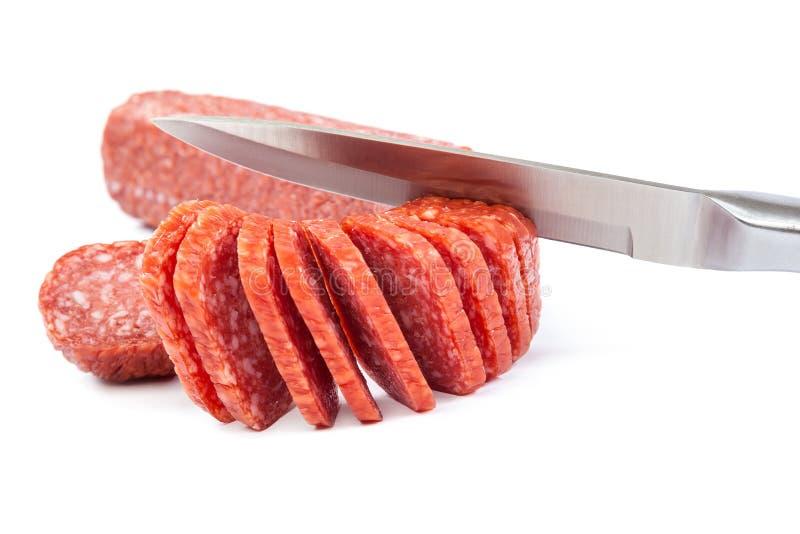 Collez la saucisse et un couteau sur un fond blanc photos stock