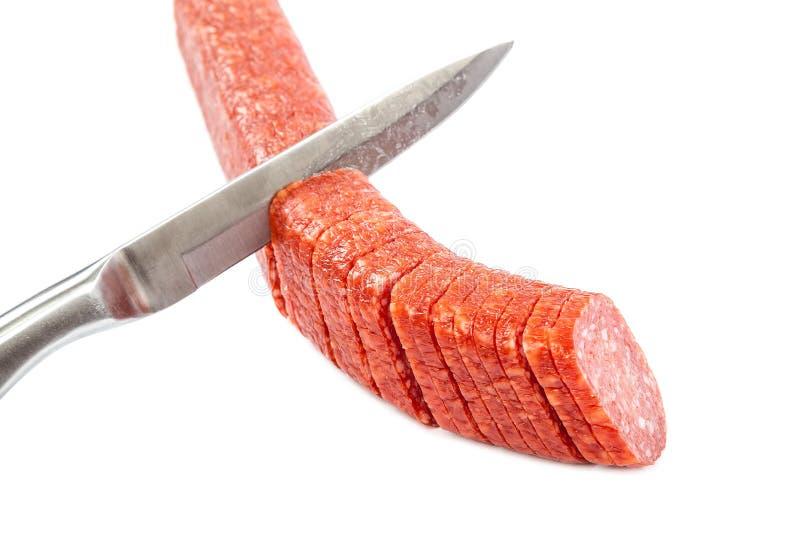 Collez la saucisse et un couteau sur un fond blanc photographie stock libre de droits