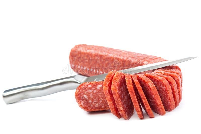 Collez la saucisse et un couteau sur un fond blanc image libre de droits