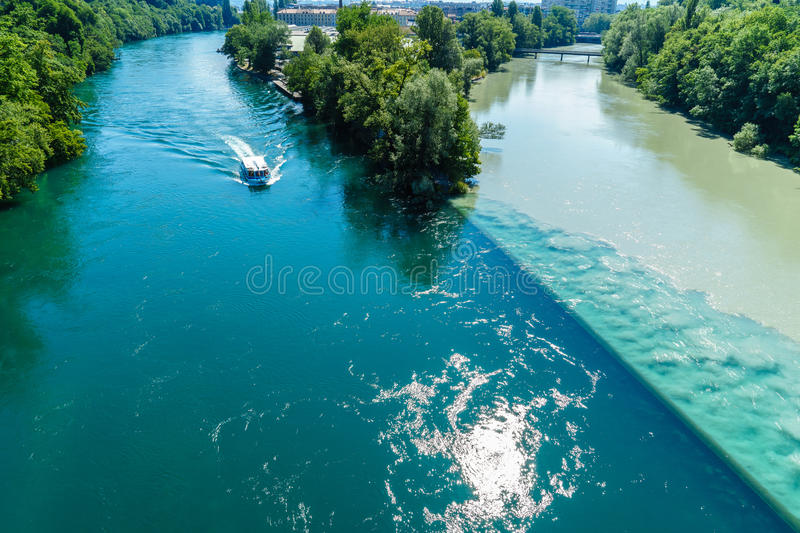 Colliding Rivers in Geneva. Two rivers junction, the Rhone and the Arve, in Geneva, Switzerland. The river on the left is the Rhone, which is just exiting Lake royalty free stock images