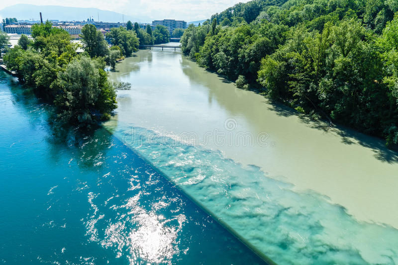 Colliding Rivers in Geneva. Two rivers junction, the Rhone and the Arve, in Geneva, Switzerland. The river on the left is the Rhone, which is just exiting Lake royalty free stock image