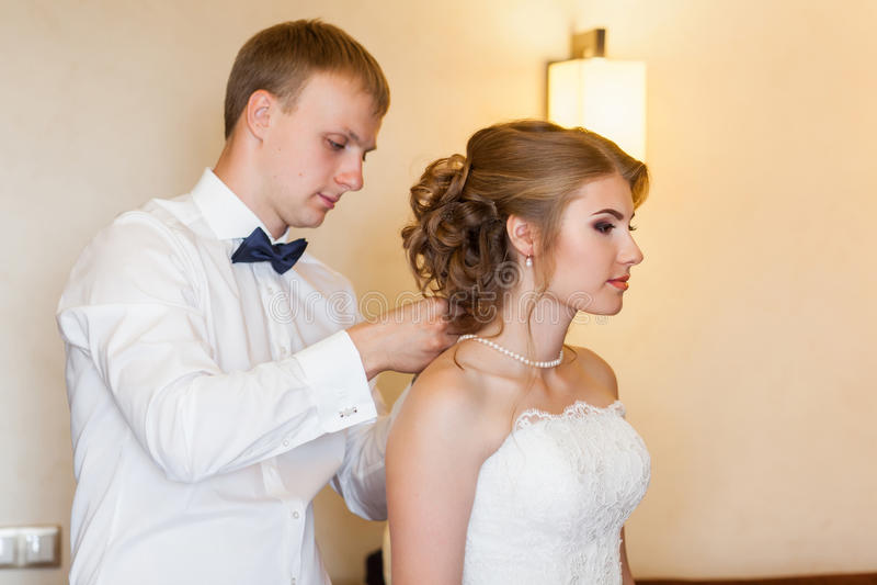 Collier accrochant de jeune marié sur le cou de la jeune mariée s photo libre de droits