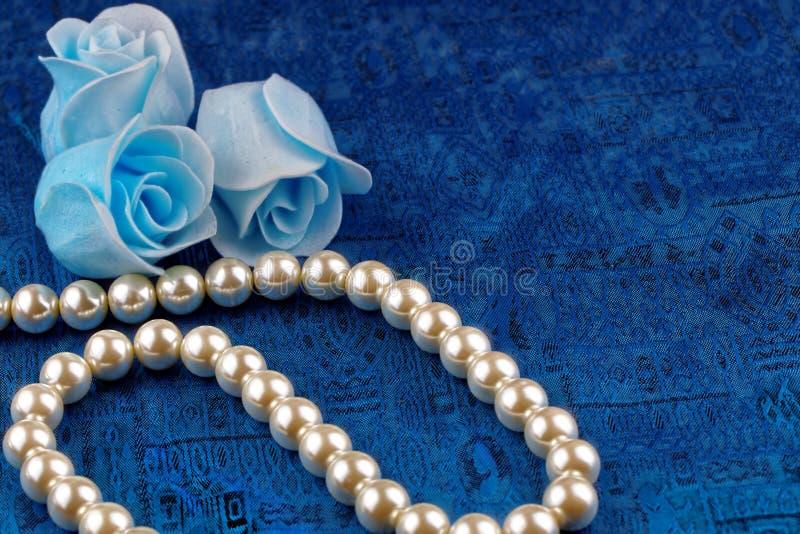 Collier de perle avec le fond bleu de satin images libres de droits