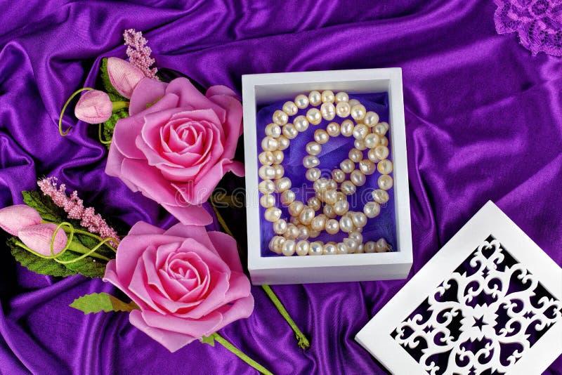 Collier de perle dans le boîtier blanc avec la fleur photo stock